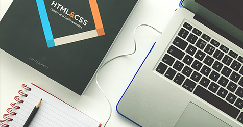 web design items including laptop, coding book and notepad