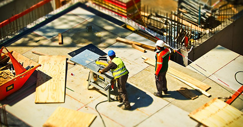 construction site with two employees in high-vis jackets